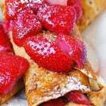 Peanut butter Nutella crepes topped with strawberries in syrup